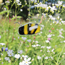 Load image into Gallery viewer, A yellow and black glass bee hangs in amongst wildflowers as if in a meadow