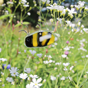 A yellow and black glass bee hangs in amongst wildflowers as if in a meadow
