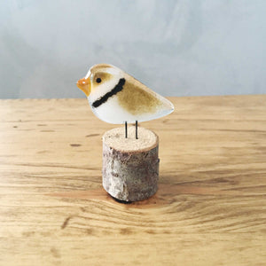 Small toonie sized glass Piping Plover bird ornament in driftwood.