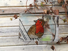 Load image into Gallery viewer, A glass tile featuring a British Robin. The tile hangs against a natural backdrop of winter clematis.
