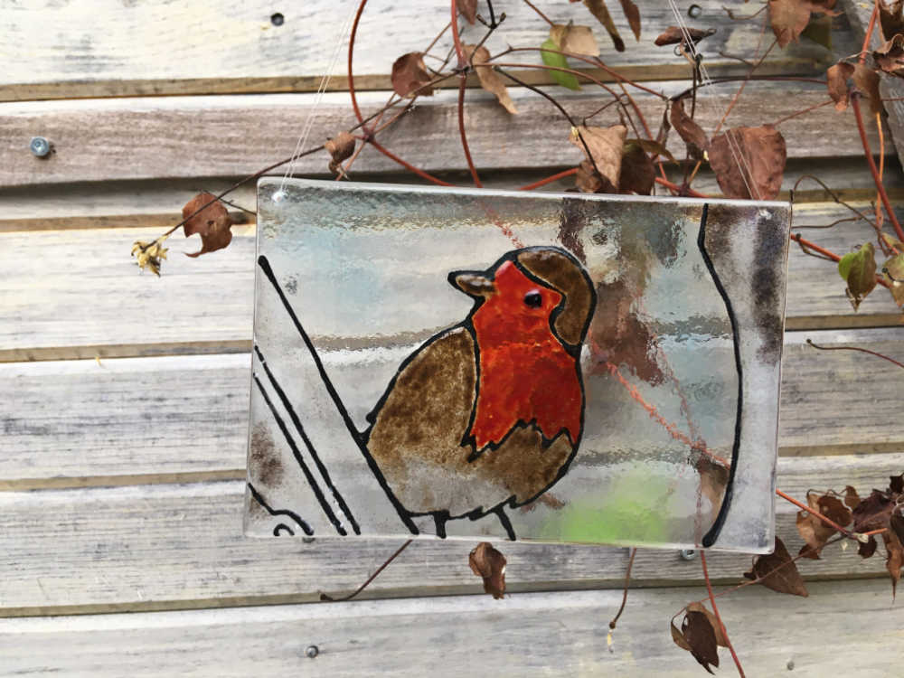 A glass tile featuring a British Robin. The tile hangs against a natural backdrop of winter clematis.