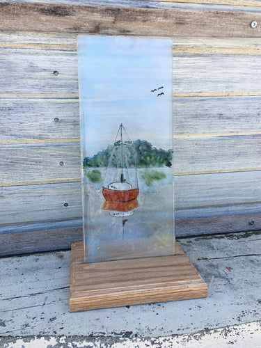 Glass picture of a red sailboat.