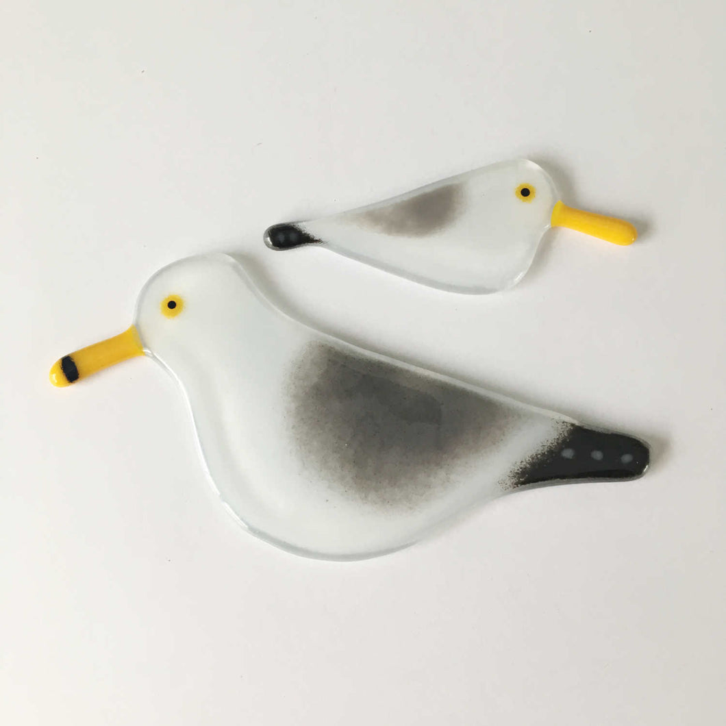 Two glass black, grey and white birds with yellow beaks, created to look like Gulls