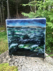 Landscape palette knife painting created from glass powders. The scene is of a turbulent ocean and a hint of the Peggy's Cove peninsula in the background.