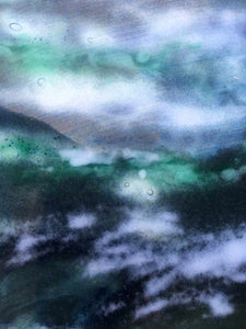 Close up photo of a glass landscape powder painting in various shades of greens, blues and browns.