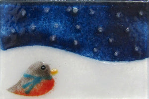 Robin on a snowy hill with a deep blue sky speckled with snowflakes: a Christmas Tree Ornament by The Glass Bakery