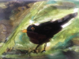 close up of a glass tile featuring a blackbird in a bush