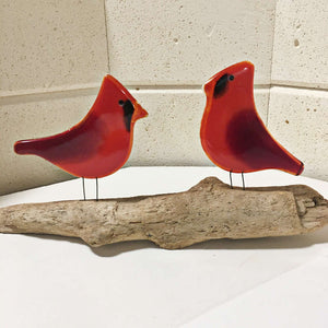 A pair of glass red birds on driftwood. The photo is taken with the walls of a glass kiln in the background