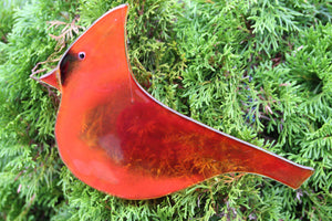 Large red glass cardinal bird hanging art piece, with cedar tree in background
