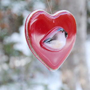 A smooth glossy red glass heart with a chickadee bird on the front