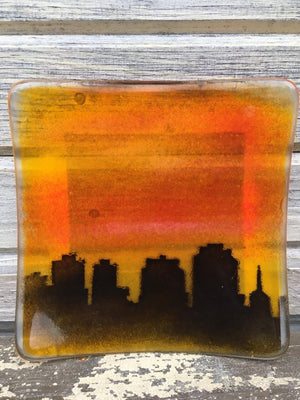An orange and black fused glass dish featuring a silhouette of the Halifax downtown skyline at sunset