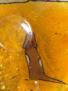Close up of amber glass dish showing brown and white dog