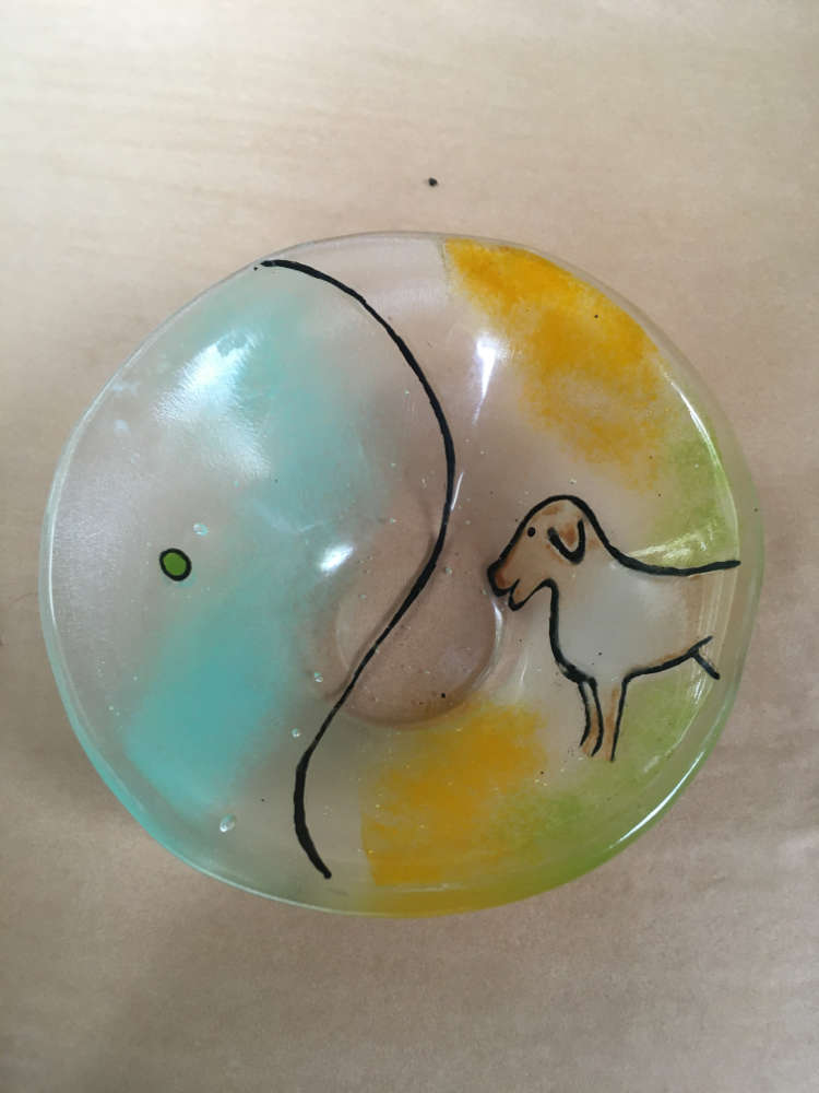 Cheerful dog looks at his green ball in the ocean - glass dish