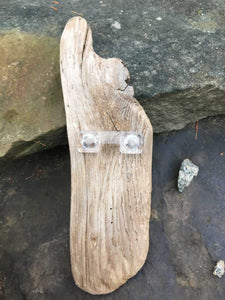An acrylic picture hook on driftwood