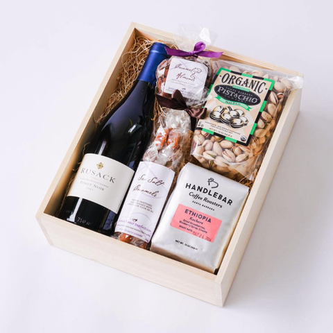 A Christmas gift box with the lid off containing wine, pistachio buts, coffee and caramels