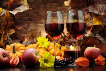 Delicious still life photo of red wine, flowers, seasonal fruit and an autumnal background.