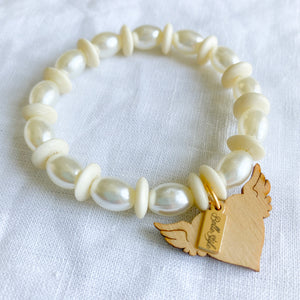 White faux pearl bone charm bracelet with rosewood hand carved flying heart bellestyle logo tag