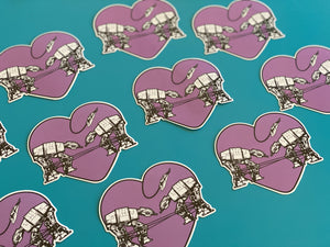 Two AT-AT Walkers facing each other and tied up. The rope tying them up is in the shape of a heart. They are falling in love. The background of the sticker is purple.  This image has 9 of the same sticker laid out on a teal background.