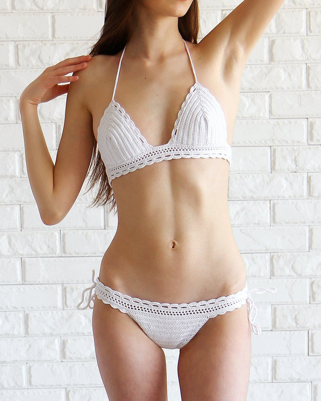 white crochet bathing suit with a delicate scalloped edge and lace detailing