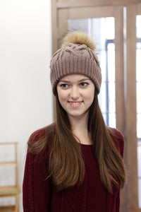 brown hand knitted hat with fur pom pom