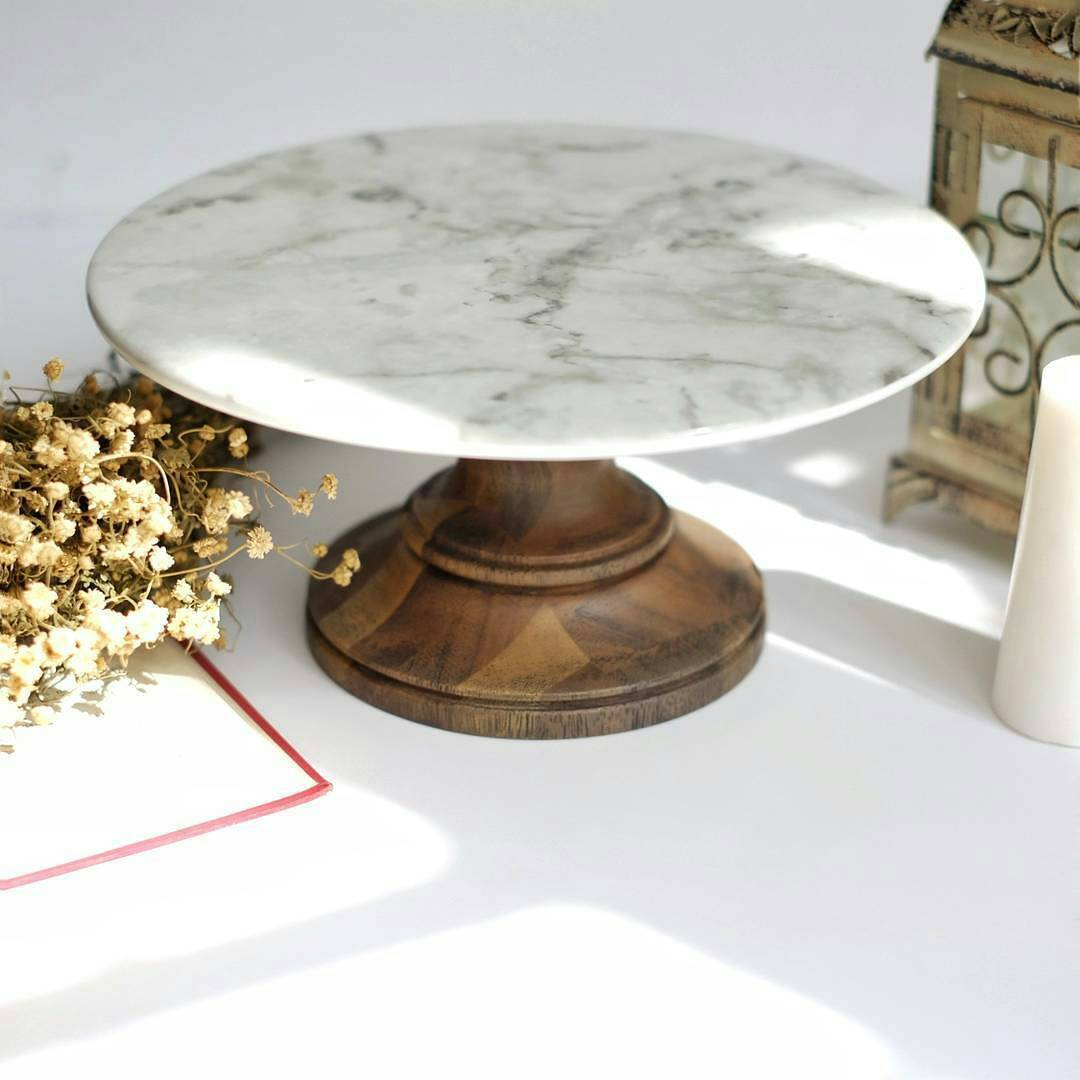 marble finish ceramic cake stand with a wooden pedestal