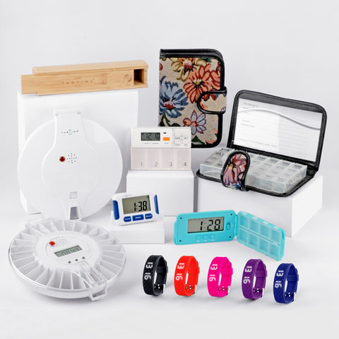 Image shows TabTime's full range of medication organiser products, including automatic pill dispenser, vibrating watch tapestry dosette box, TabTime 4, TabTime Super 8, bamboo pill box