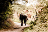 Two elderly people walking through a wood side by side in order to support the lady with dementia