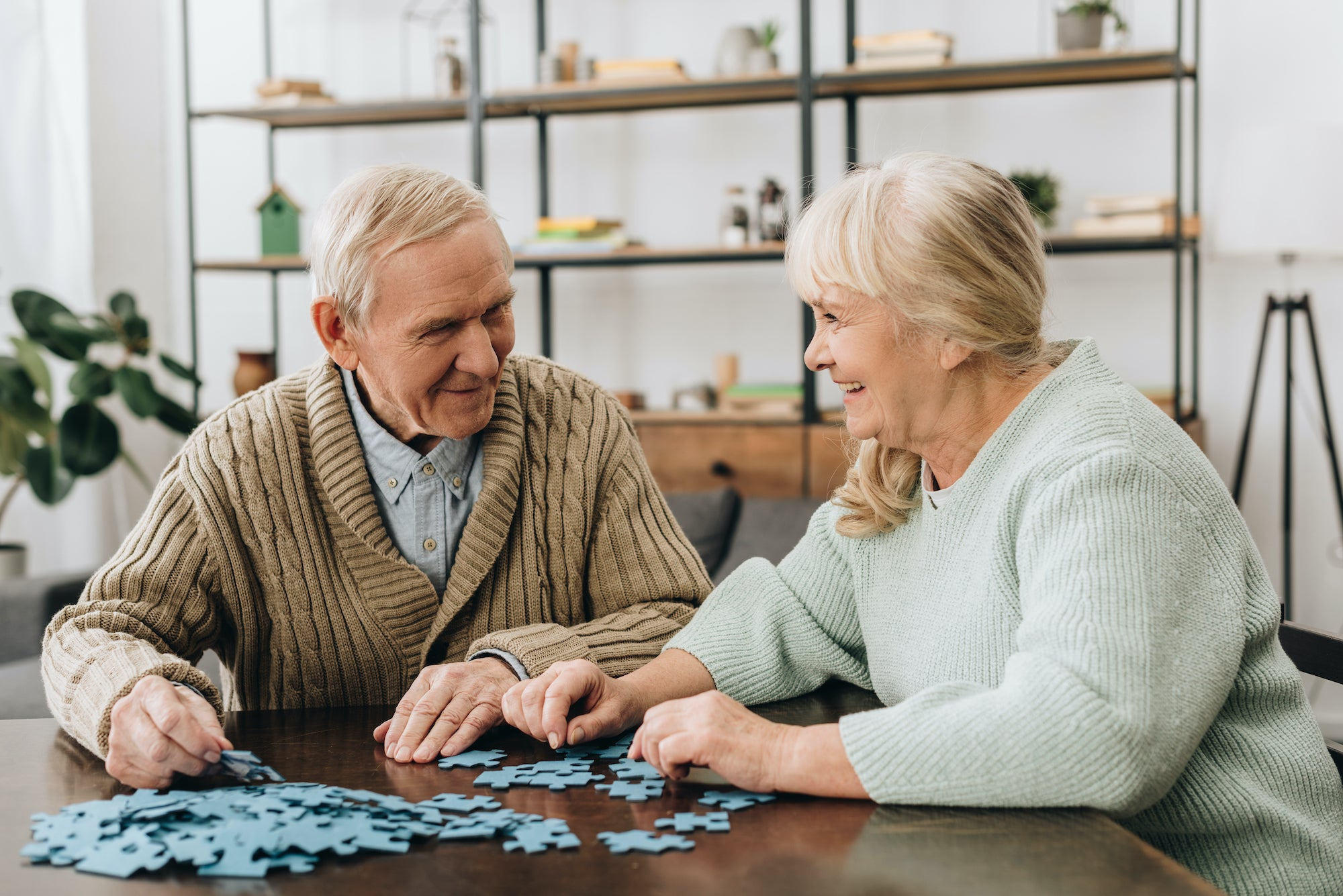 A woman helps a man complete his dementia puzzle as they sit at a brown table together
