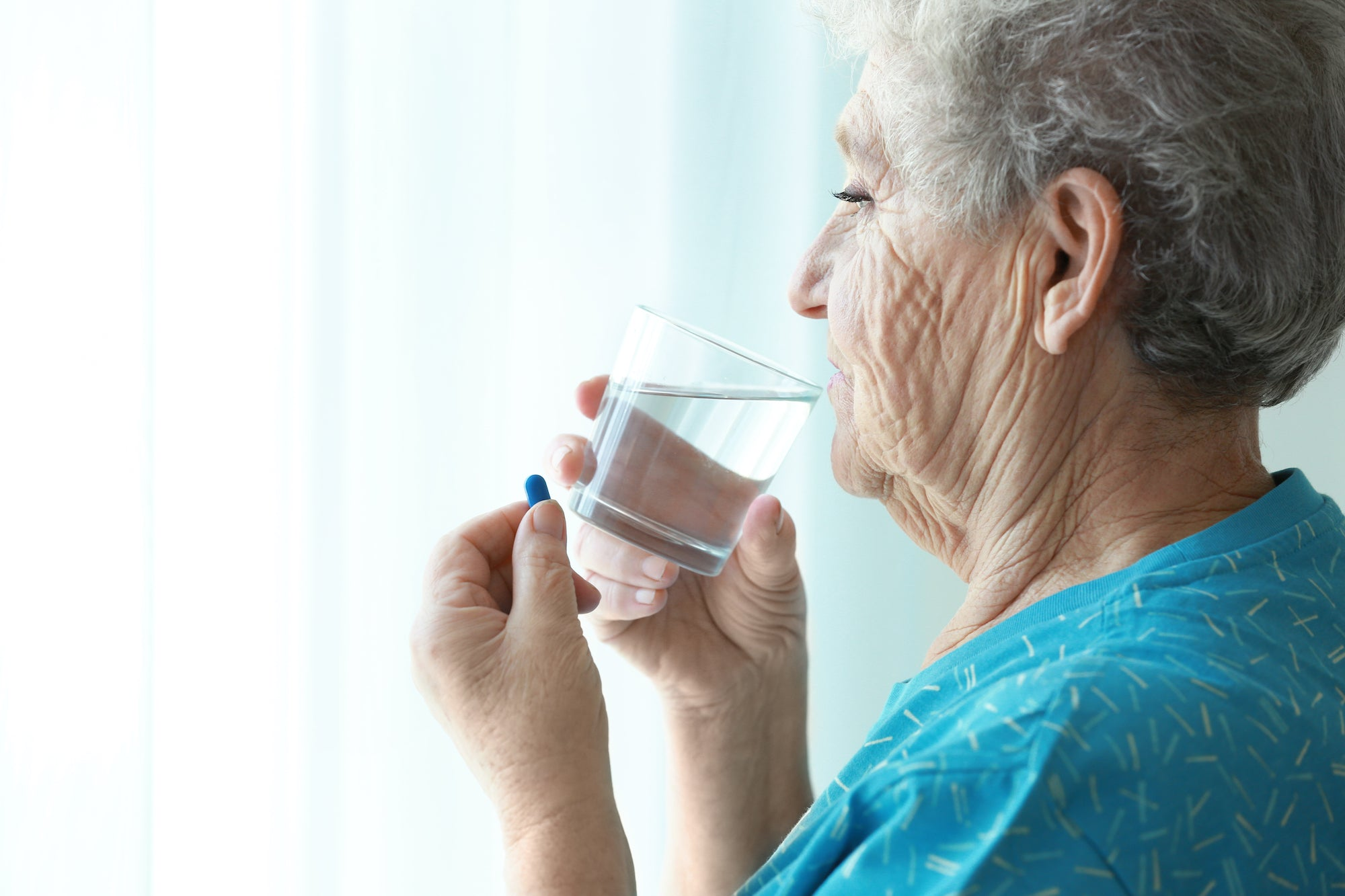 A woman drinks water from a glass due to her droplet hydration reminder as she stares out a window taking her dementia medication
