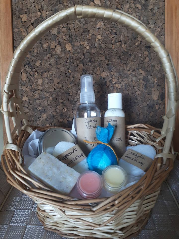 wicker basket filled with a coconut lip balm shimmer balm healing skin salve soap sunscreen bug spray