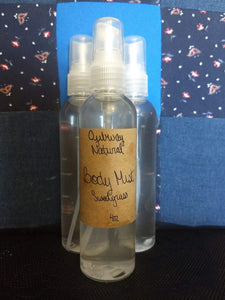 spray bottle with clear liquid brown craft paper label reading ojibway natural body mist sweetgrass