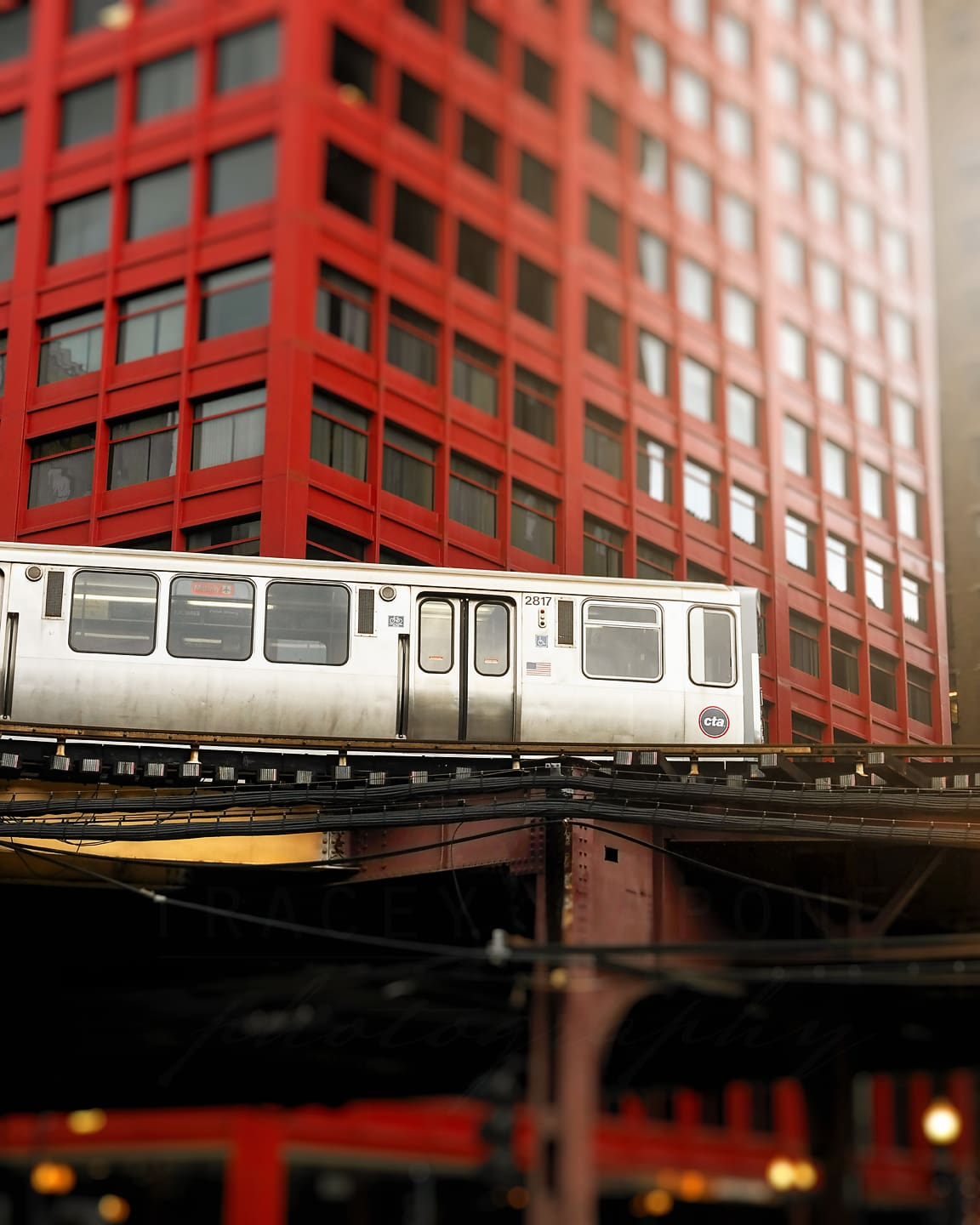 A CTA running along the elevated tracks in front of the red CNA building in downtown Chicago. Photography by Tracey Capone