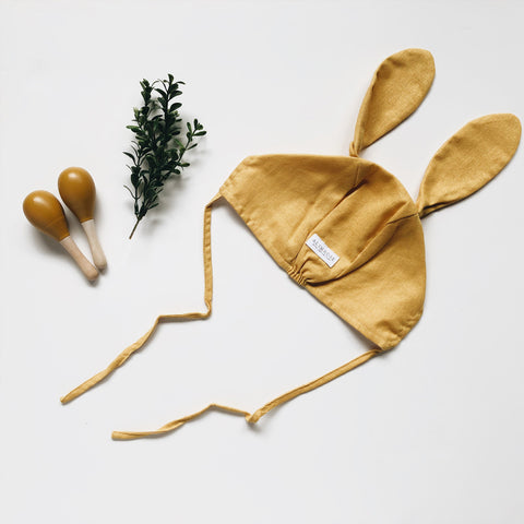 bunny bonnet with mustard baby maracas wooden toy