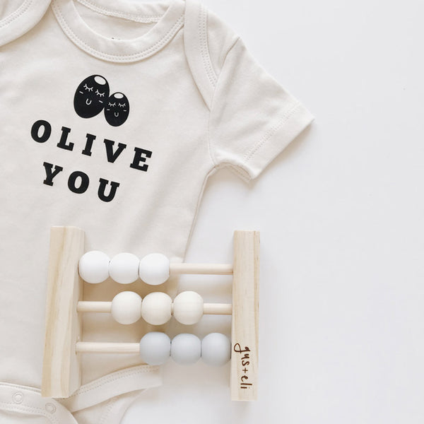 Olive You Organic Romper with wooden baby abacus toy