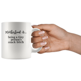 Motherhood is being a tiny person's snack bitch white coffee mug
