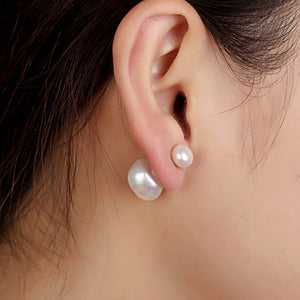 White double sided pearl earrings worn by the model, smaller pearl to the front | Orchira
