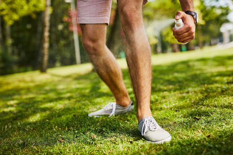 Close-up of man's legs being sprayed with insect repellent in the park