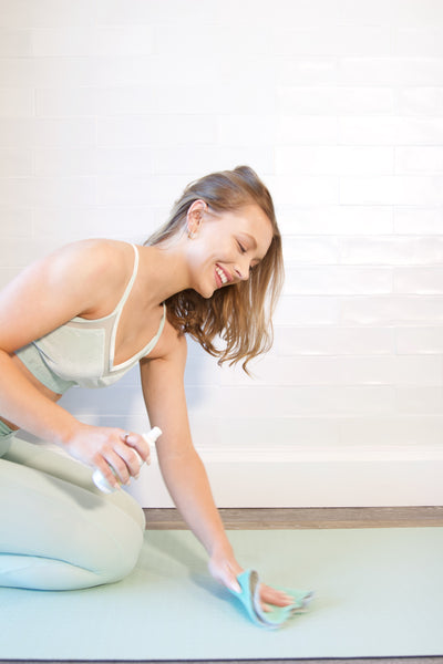 Girl Using MOXE Yoga Mat Cleaning Spray
