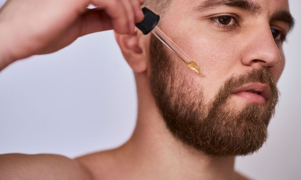 Shirtless guy adding oil drops on his beard