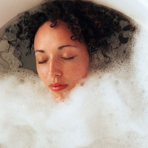 Girl using an essential oil bubble bath to help with PMS Symptoms