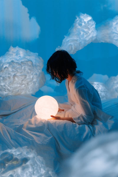Girl holding globe in abstract dream world with clouds