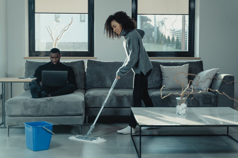 Wife mopping floors with essential oils solution while her husband is working on the couch.