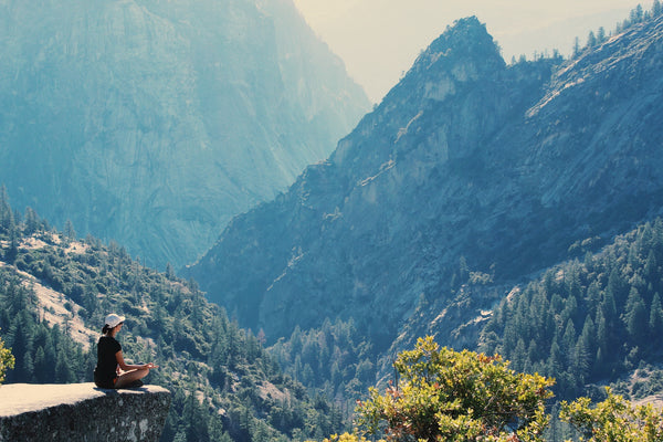 woman meditating near white fir trees from which white fir essential oil is extracted