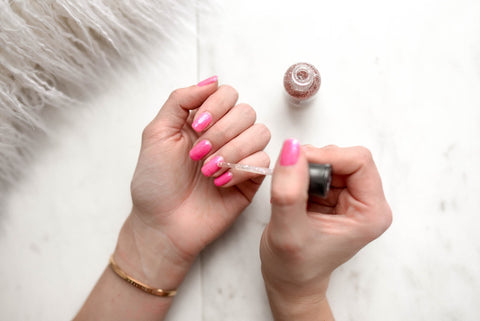 woman applying cuticle oil with lavender and myrrh essential oils to help with nails and dry cuticles
