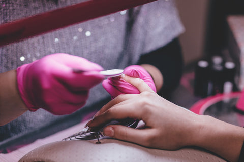 woman damaging her nails and cuticles with acrylic application during a manicure which can be resolved by using essential oils for nails and dry cuticles