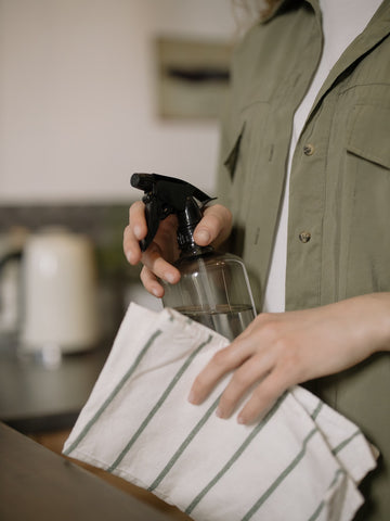 woman using 70% alcohol sanitizer to disinfect kitchen countertops