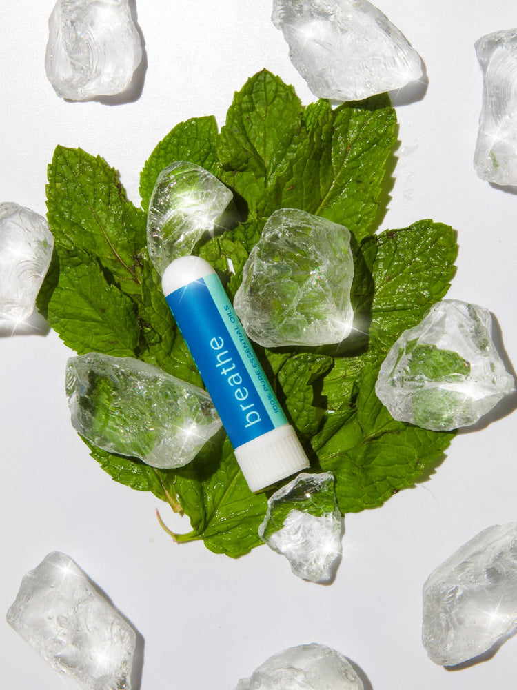 MOXĒ Breathe Nasal Inhaler on Fresh Mint Leaves