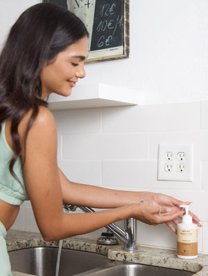 Girl washing her hands using MOXĒ Vanilla Almond Hand Soap