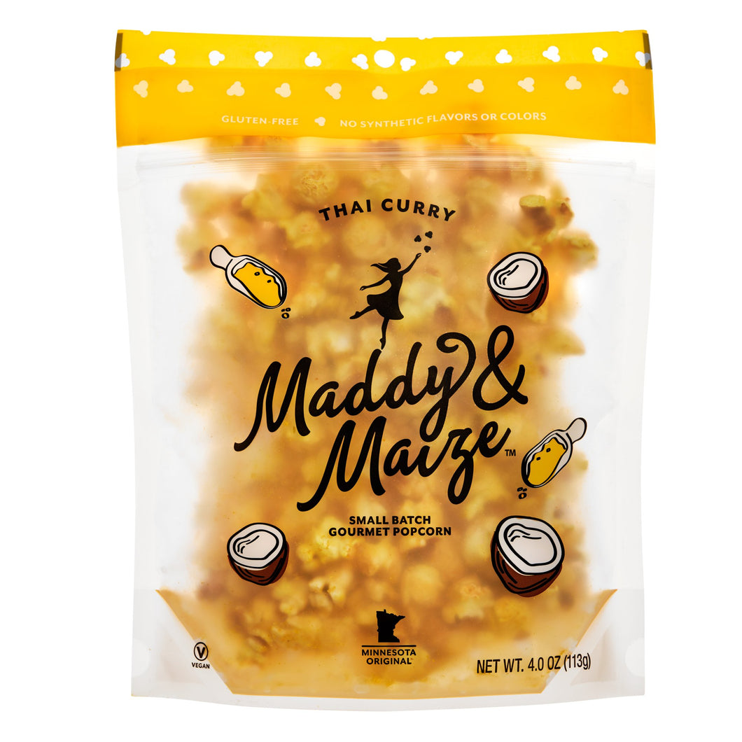 Image of one 4 ounce bag of Thai Curry popcorn. Bag is transparent and seasoned popcorn with a yellow color is visible. Maddy & Maize logo is large and centered on bag. Packaging includes drawn graphics of coconuts and curry seasoning.