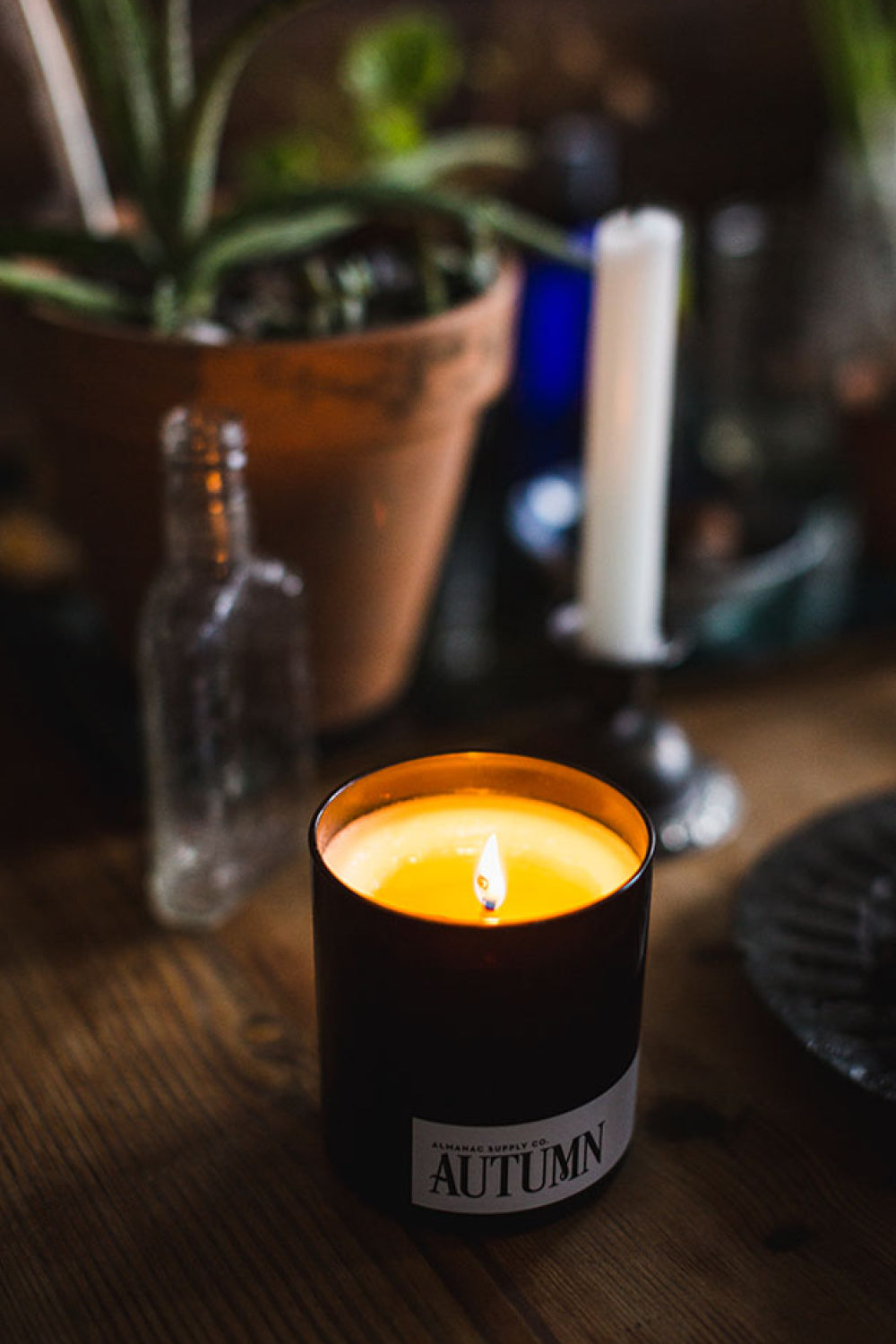 Lit Autumn Candle on wooden countertop